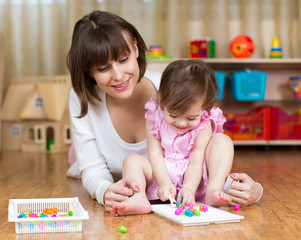 mom and her kid girl play toys in children room
