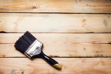 Hand holding big paintbrush over wood background