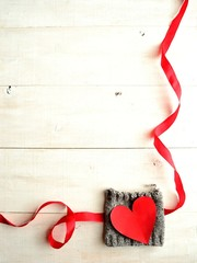 Red heart on knit with red ribbon