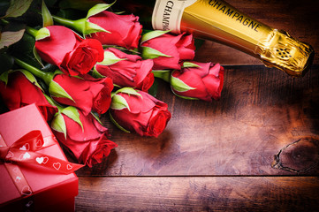 Valentine's setting with red roses, champagne and gift