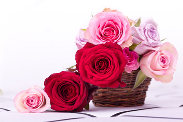 pink and red roses in brown basket