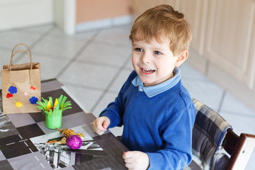 Little toddler boy being happy about selfmade Easter egg in kind