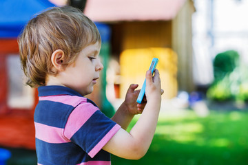 Beautiful little boy taking picture with mobile in summer garden