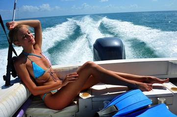 Girl relaxing on the back of motor boat
