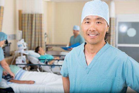 Smiling Male Nurse Standing In Hospital Ward