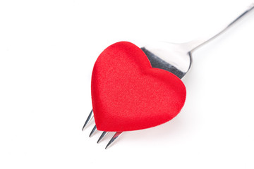 red heart on a fork, close-up, isolated