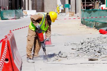 A laborer uses a jackhammer to break up a concrete pavement