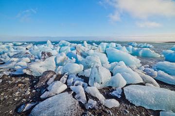 Ice blocks on a sand beach.