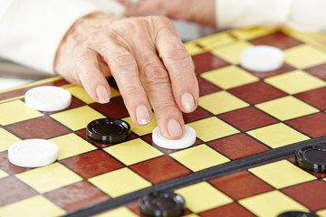 Wall Mural - Hand einer Seniorin beim Dame spielen