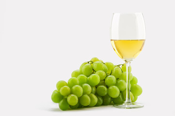 glass of white wine and green grapes on a white background