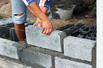 Worker construction laying concrete blocks  on wall project