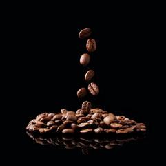 Falling coffee grain against black wall.