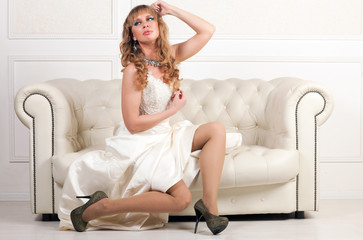 woman in white dress sitting on a sofa