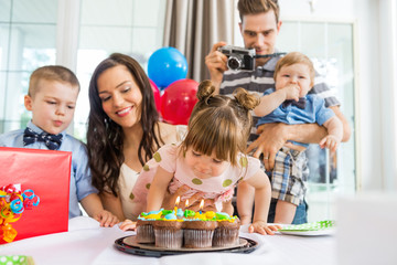 Family Celebrating Girl's Birthday At Home