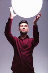 man reaching out to a big ball of light