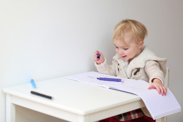 Happy blonde toddler girl drawing with colorful crayons