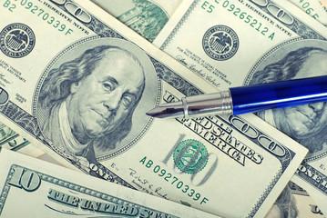 blue pen on dollars background