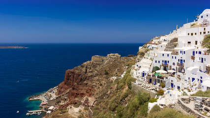 white houses and old  fortress on the red rock . Santorini.