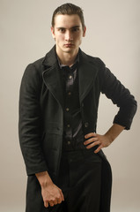 Beautiful man wearing a black shirt, pants and a long coat