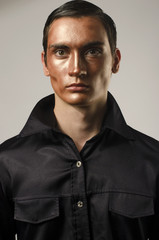 Sexy man wearing make up, dressed in a black shirt