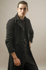 Businessman dressed in black shirt,pants and wearing a long coat