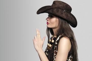 American cowgirl with cowboy hat blowing fingers in gun shape