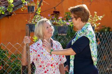 Two elderly ladies chatting in the garden.