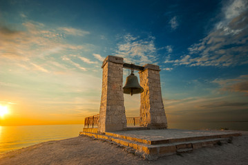 bell at sunset near the sea