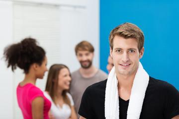 sportlicher mann mit freunden im fitness-studio