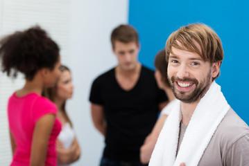 lächelnder mann mit freunden im fitnesscenter