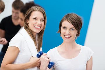 zwei glückliche frauen im fitnesscenter