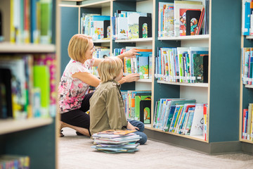Teacher Assisting Boy In Selecting Books In Library Wall mural
