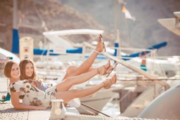 Beautiful girl sitting on the dock near the sea