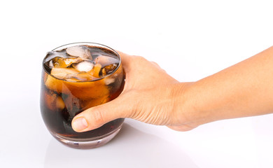 Female hand holding a cola drink in a short glass