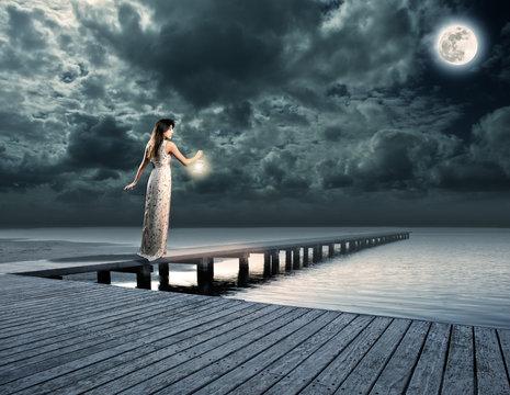 woman holding a lantern on a wharf