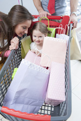 Close-up of young daughter in trolley being pushed by father and mother