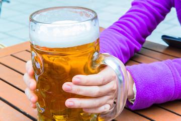 hand holding a full mug glass of beer
