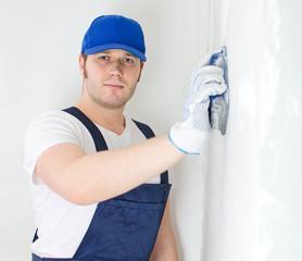 Male plasterer in baseball cap polishing the wall.