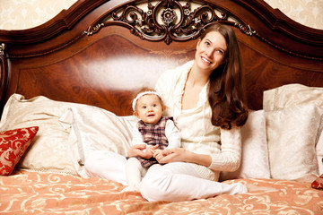 Young family in the bedroom. Mother and daughter in the interior