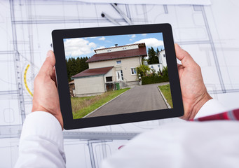 Male Architect Holding Digital Tablet Over Blueprint