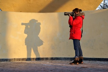 Photographer, woman with a camera and its shadow