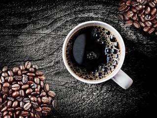 Full roast coffee beans with freshly brewed coffee