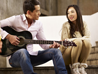 young man playing guitar and singing for girlfriend