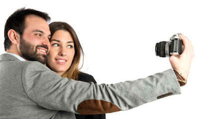 Man photographing with his girlfriend over white background