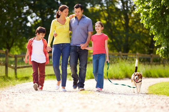 Hispanic Family Taking Dog For Walk In Countryside
