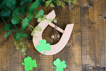 Horseshoe and clover on wooden table close-up
