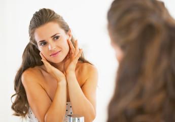Young woman checking facial skin condition