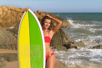 Beautiful sexy young woman surfer girl in bikini with surfboard