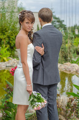 The couple in the garden. bride looks in the picture