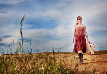 Muchacha sonriente con maleta en la mano.Viajes